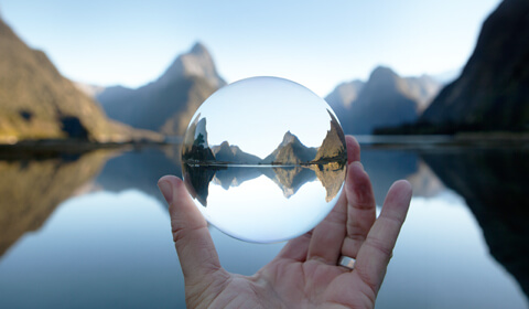 Photograph of hand holding glass sphere that magnifies mountain and lake scenery