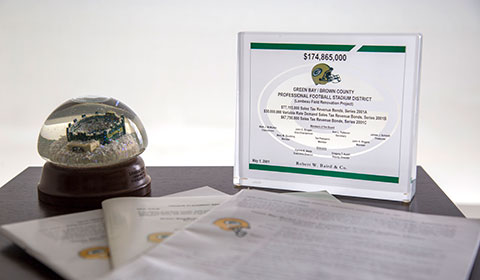 Photograph featuring: a Lambeau Field snowglobe, placard regarding Lambeau Field Renovation Project deal, copies of the final official statement regarding the project deal with Baird.