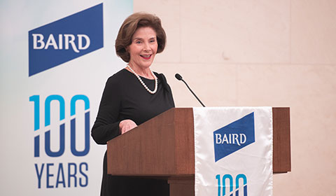 Laura Bush stands speaks at podium.