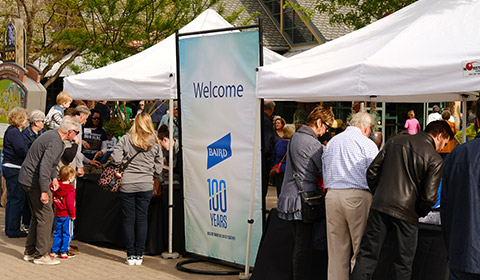 Photo of various Baird associates and their families checking in at tents at the Denver Zoo.