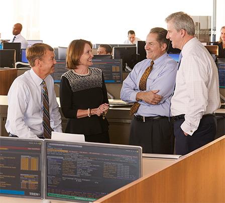 Photo of four Baird Asset Management Associates meeting