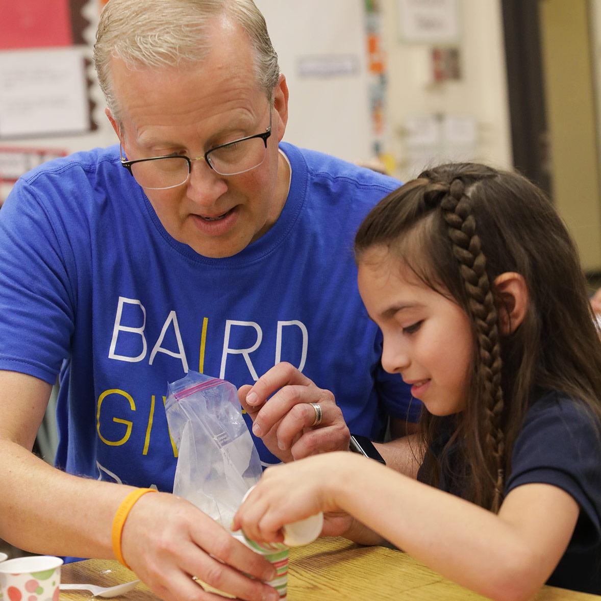 Baird volunteer helps student with art project