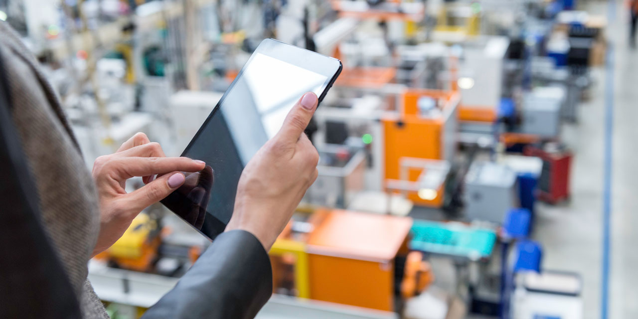 Woman clicking on iPad to activate screen in a warehouse
