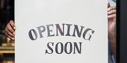 Man hanging opening soon sign in window
