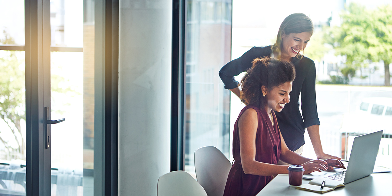 Shot of two young businesswomen using a laptop together at work