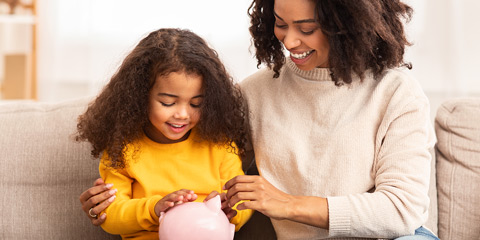 Mom and daughter holding piggy bank.