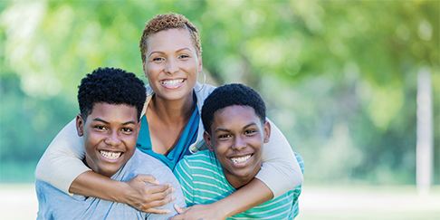 African-American mother smiling while hugging two young sons.