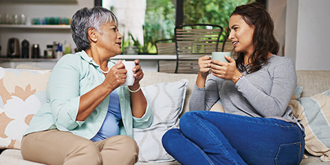 Mature mother and daughter discussing finances over coffee.