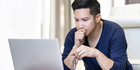 Man concentrating while looking at laptop