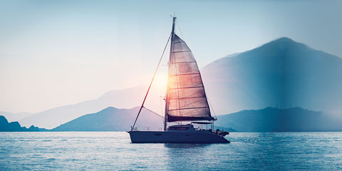 Sailboat on calm lake surrounded by mountains.