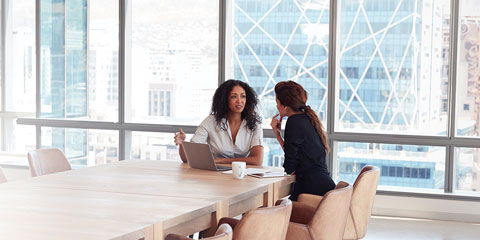Two women discussing plans in a large conference room.