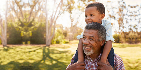 Black grandfather carries grandson on shoulders during walk in park