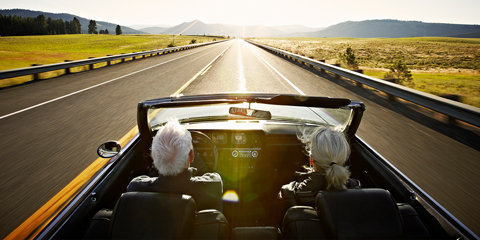 Retired Couple Driving Convertible Into Sunset