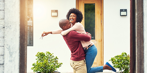 Couple hugging in front of house