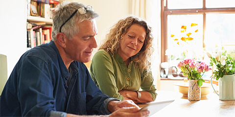 Middle-aged couple sitting at kitchen counter reviewing documents on a laptop.