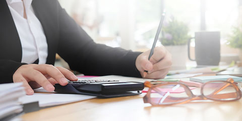 Woman writing with pencil and paper and typing into calculator.