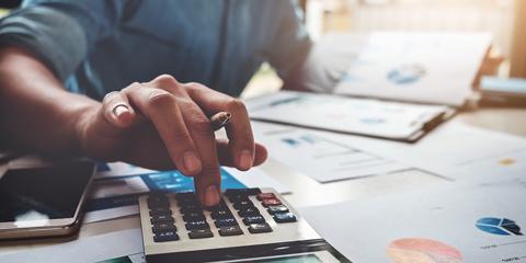 Close-up of man using calculator