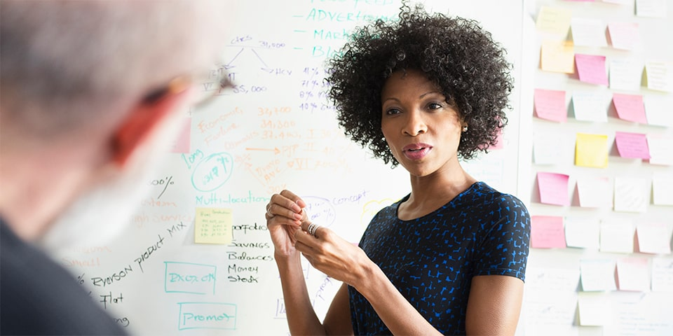 Female African-American next to meeting room white board full of notes and post-its, speaking to another individual.