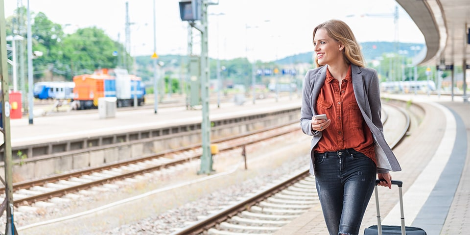 Blonde woman, smiling, whil walking along train platform.