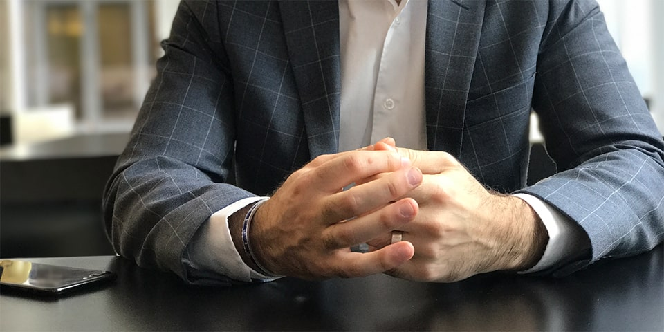 Faceless man, sitting at table with hands folded.