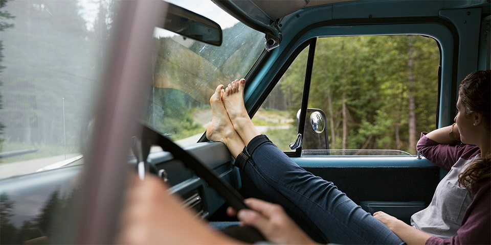 Young female sitting in passenger's seat with feet on car's dashboard.