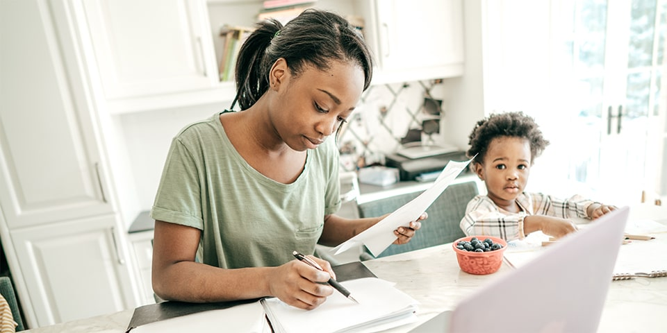 African-American woman sitting at counter going over documents with infant in high-chair next to her.