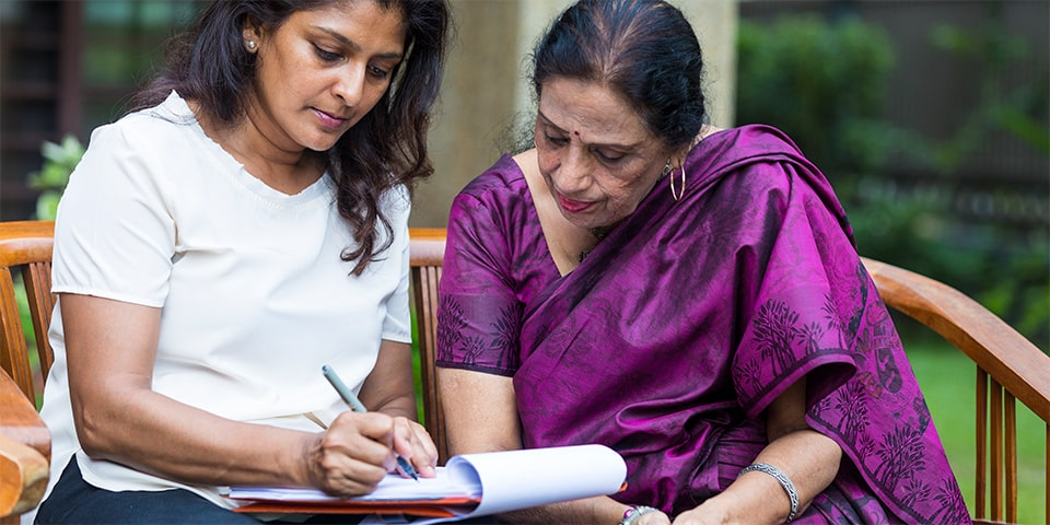 Malaysian mother and daughter going over financial documents.