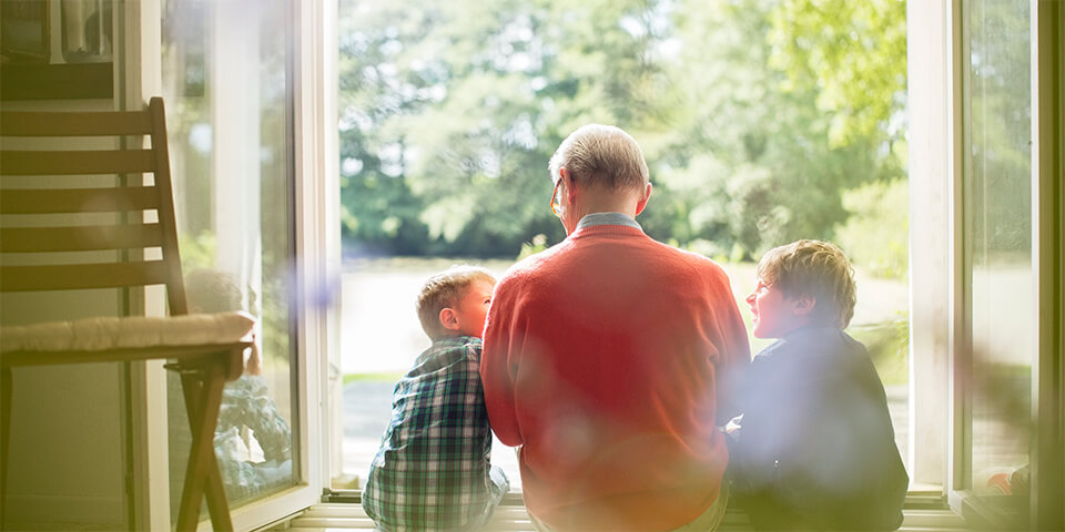 Grandfather sitting with grandchildren in door opening to outside.