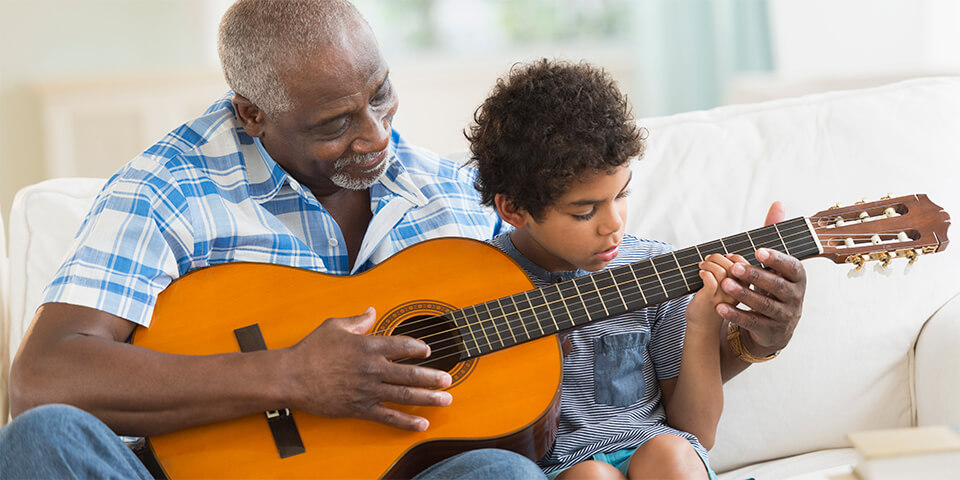 Grandfather teaching grandson how to play guitar.