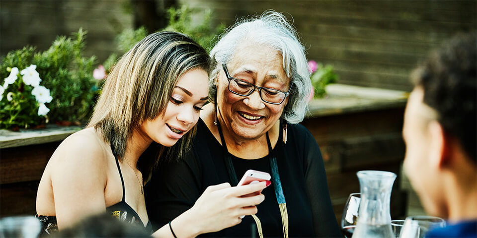 Grandmother and granddaughter looking at a phone's screen.