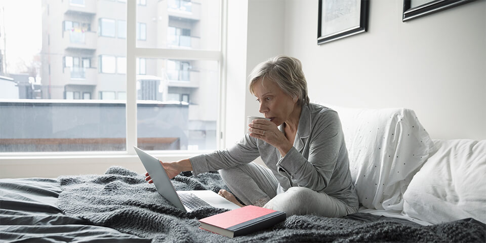 Grey-haired woman, sitting in bed and sipping coffee as she looks at laptop screen.