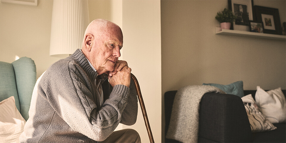 Elderly man sitting, leaning on cane in deep though.