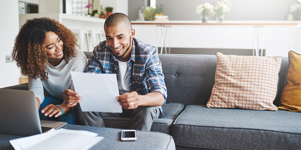 Young, bi-racial couple looking over documents in front of laptop on couch.