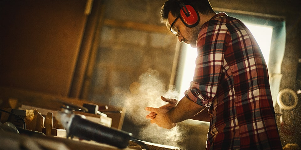 Brunette male wearing protective headphones while wood-working.