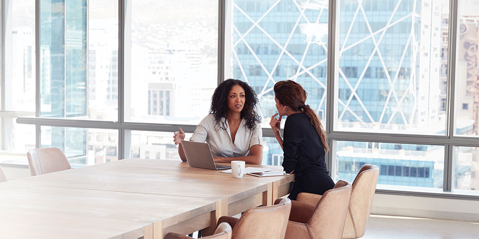 Two females seated at end of conference table in front of window conversing.