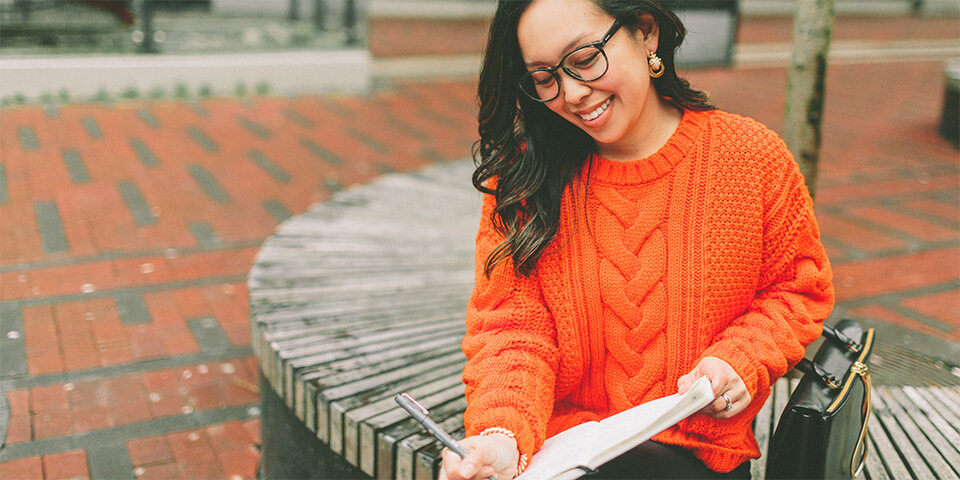 Young Asian-American writing in notebook wearing an over-sized orange sweater.