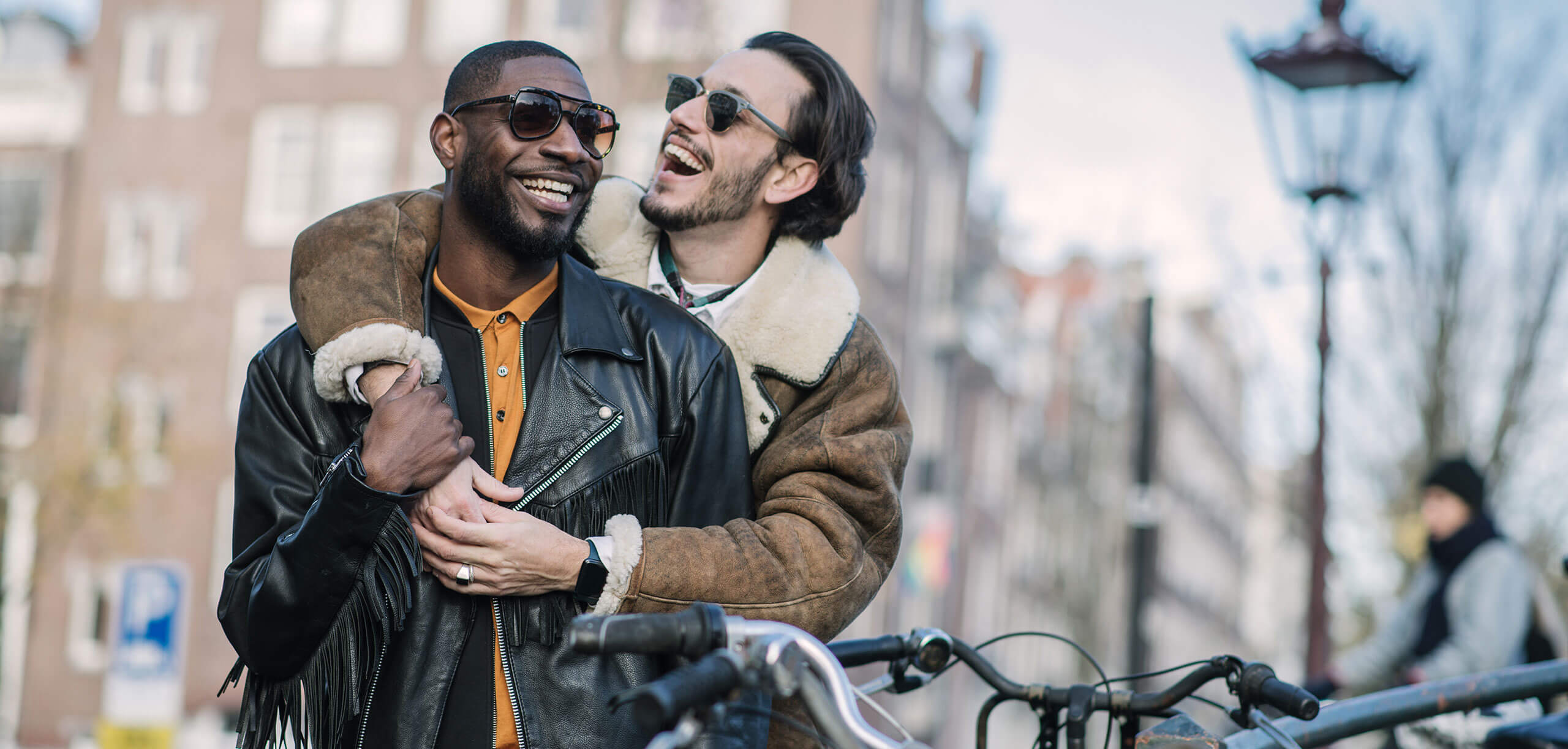 Same-sex couple embraced on street in late autumn or early winter in Amsterdam. Caucasian and African ethnicity, brown hair, sunglasses, wearing leather jackets.