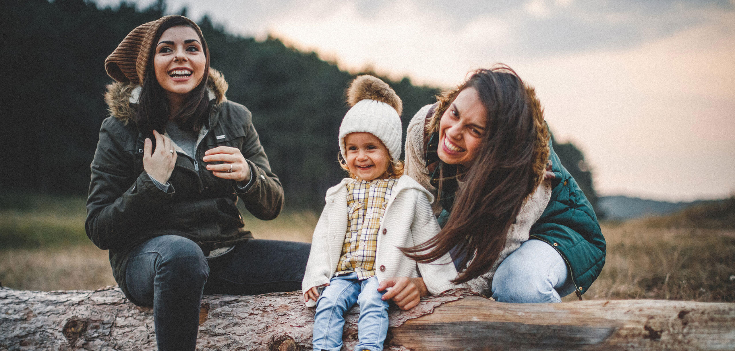 Same-sex couple enjoying nature with their toddler daughter. Caucasian or Hispanic ethnicity, brown hair, wearing jackets, hats, and hiking boots. Late Autumn day.