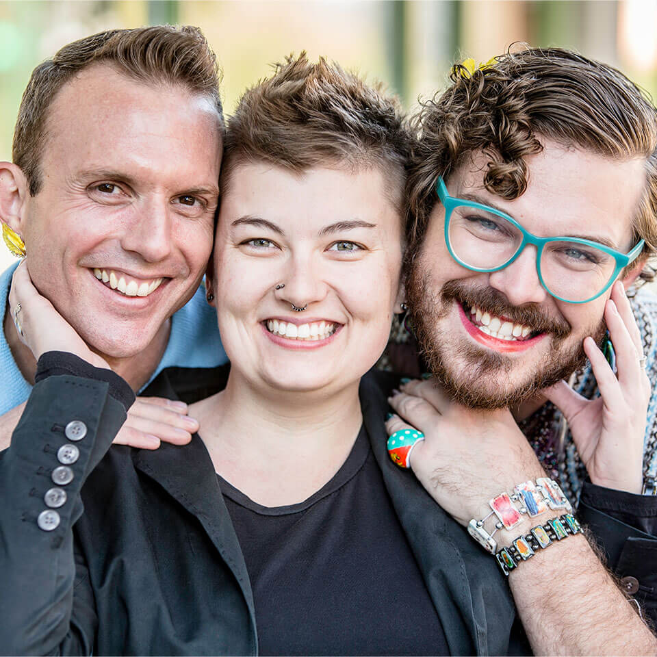 Three gender fluid friends pose and smile for photo.