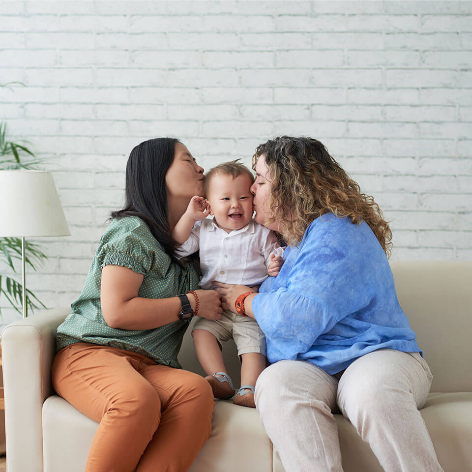 Same-sex couple kissing their smiling toddler on both cheeks. Asian and Caucasian ethnicity, dark brown and curly, blonder hair. Living room with lots of natural light.