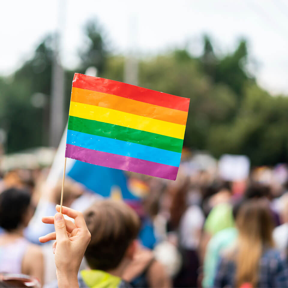 Rainbow flag at pride parade with blurred participants in the background