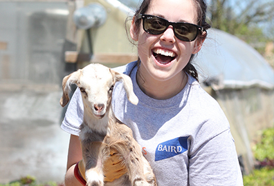 Photo of Baird associate with baby goat during Baird Gives Back Week.