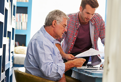 Photo of father and son going through important documents and paperwork.