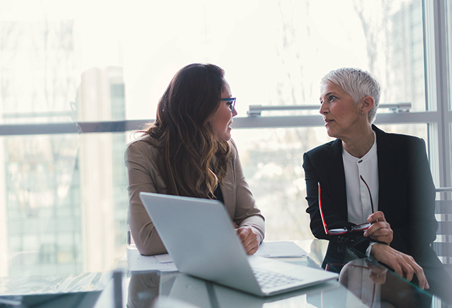 Older and younger woman conversing in an office