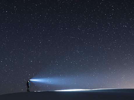 Holding flashlight to the night sky