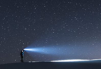 Holding flashlight to the night sky