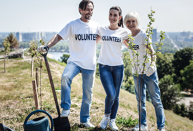 Couple volunteering outside with mother-in-law