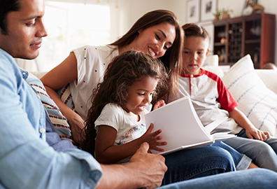 Mother and father reading to daughter and son on couch