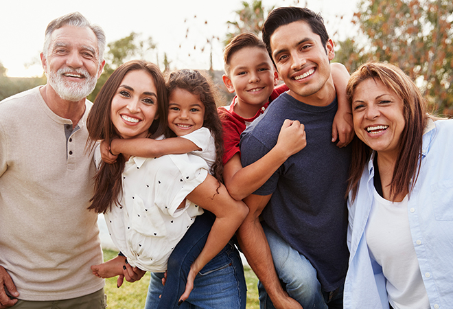 Multigenerational family standing outside in a line hugging