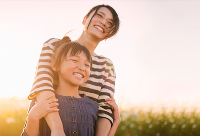 Smiling Asian-American mother holding daughter.